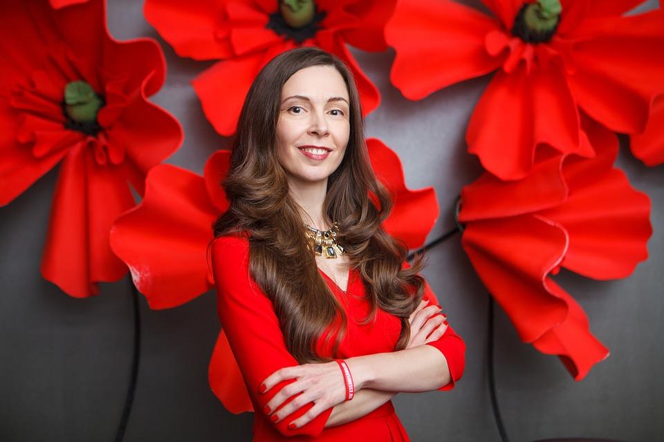 Девушка в красном платье на фоне красных цветов