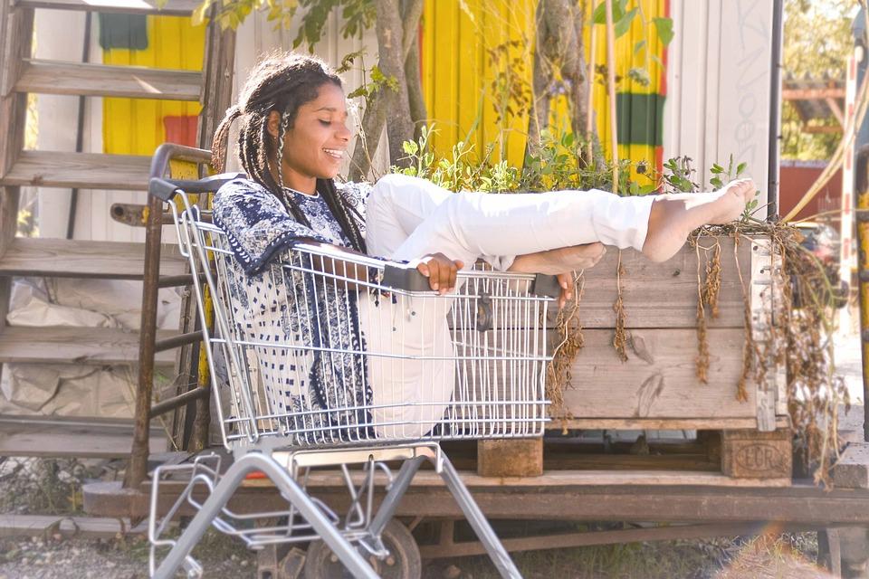Девушка сидит в тележке из супермаркета