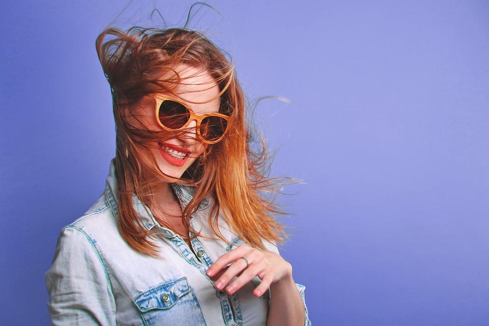 Девушка на лиловом фоне в очках улыбается